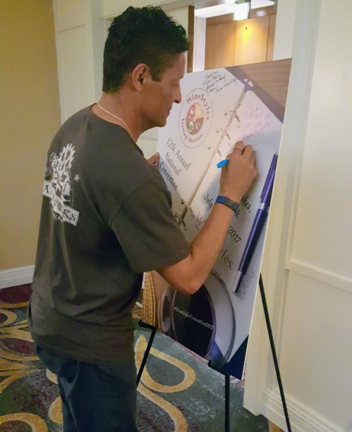 Bob signing the annual Convention poster